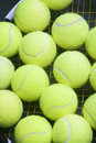Plenty of tennis balls on raquet strings against black background vertical image Stock Photography