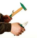 Pliers, a spanner and a hammer in the hands of the working man Royalty Free Stock Photo