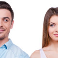 They are plotting something beautiful young loving couple smiling and looking at each other while standing against white Stock Image