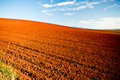 Ploughed agricultural fields red earth in newly turned and under a blue summer sky in a beautiful australian landscape Stock Photo