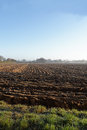Ploughed field view across a plowed early on a winter morning an ideal rural background Royalty Free Stock Photo