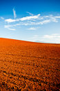 Ploughed red earth in late evening sun glowing richly the golden light a beautiful environmental landscape of agricultural Stock Photo