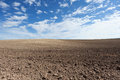 Plowed field with blue sky and beautiful clouds Stock Photography