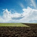 Plowed fields under cloudy sky green and Royalty Free Stock Images