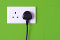 Plugged in socket against green tiles background a electrical pin plug into wall Royalty Free Stock Photo