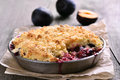 Plum crumb tart in pan on wooden background Royalty Free Stock Images