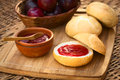 Plum jam on bun spread with plums in basket wooden board photographed with natural light selective focus focus the front of Stock Photo
