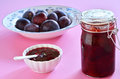 Plum jam fresh homemade with raw plums on deep pink background Royalty Free Stock Image