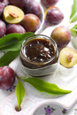 Plum jam in a glass jar and fresh fruits with leav Stock Images