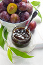 Plum jam in a glass jar and fresh fruits with leav Royalty Free Stock Image