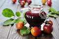 Plum jam in a glass jar and fresh fruits with leaves on wooden background closeup Royalty Free Stock Photo