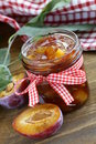 Plum jam in jar on wooden table Stock Photos