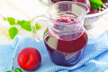 Plum juice in glass jug Stock Photo