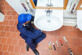 Plumber with cap repairing sink in public bathroom Stock Image