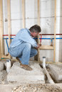 Plumber contractor construction worker working finishing touches installing pipes lines hot cold running water red blue lines used Royalty Free Stock Photography