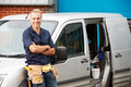 Plumber or electrician standing next to van with arms crossed smiling Stock Photo