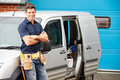 Plumber or electrician standing next to van looking camera with arms crossed smiling Royalty Free Stock Image