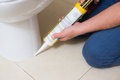 Plumber fixing toilet in a washroom with silicone cartridge Royalty Free Stock Photo