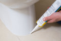Plumber fixing toilet in a washroom with silicone cartridge close up of Stock Photo
