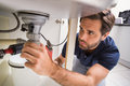 Plumber fixing under the sink in kitchen Royalty Free Stock Images