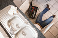Plumber fixing under the sink in kitchen Stock Image