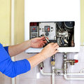 Plumber gas heating repairman fixing a with screwdriver Stock Photography
