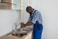 Plumber pressing plunger in sink young male african kitchen Royalty Free Stock Photos