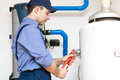 Plumber repairing an hot water heater while Royalty Free Stock Images
