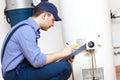 Plumber repairing an hot water heater technician Stock Photography