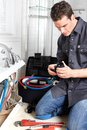 Plumber young handsome doing reparation of water tap Royalty Free Stock Photos
