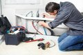 Plumber young handsome repearing bath tub service Stock Photography