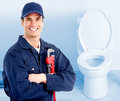 Plumber young near a flush toilet Royalty Free Stock Photos