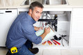 Plumber young smiling fixing a sink in the kitchen Royalty Free Stock Images