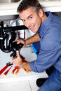 Plumber young smiling fixing a sink in the kitchen Royalty Free Stock Photography