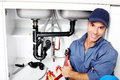 Plumber young smiling fixing a sink in the kitchen Stock Images