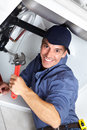 Plumber young smiling fixing a sink in the kitchen Royalty Free Stock Photos