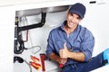 Plumber young smiling fixing a sink in the kitchen Royalty Free Stock Photo