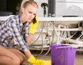 Plumbing woman mopping up she is calling to Royalty Free Stock Images