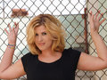 Plump blond woman against chain linked fence Stock Photos