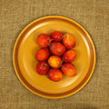 Plums on plate a closeup of golden a a hessian background Stock Photo