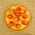 Plums on plate a closeup of golden a a hessian background Stock Image