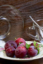 Plums on a plate and tea utensils the wooden background Royalty Free Stock Photos