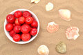 Plums and shells red on sand Stock Image