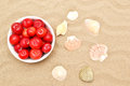 Plums and shells red on sand Stock Photos