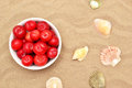 Plums and shells red on sand Stock Photo