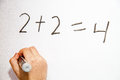 Plus equals girl hand writing and doing simple calculation on whiteboard Royalty Free Stock Photography