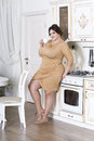 Plus size fashion model on kitchen, fat woman on luxury interior, overweight female body Royalty Free Stock Photo