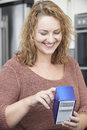 Plus size female reading nutritional information on packet in kitchen Stock Photo