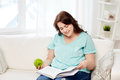 Plus size woman with book and apple at home healthy eating organic food fruits diet people concept happy young reading eating Stock Image