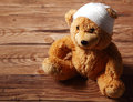 Plush Brown Teddy Bear with Bandaged on the Table Royalty Free Stock Photo